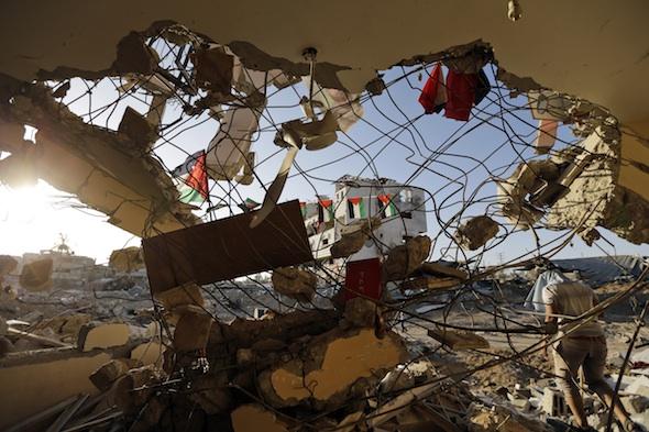 A Palestinian walks away from his house, destroyed by an Israeli strike, in the Gaza City neighborhood of Shijaiyah. AP/Lefteris Pitarakis