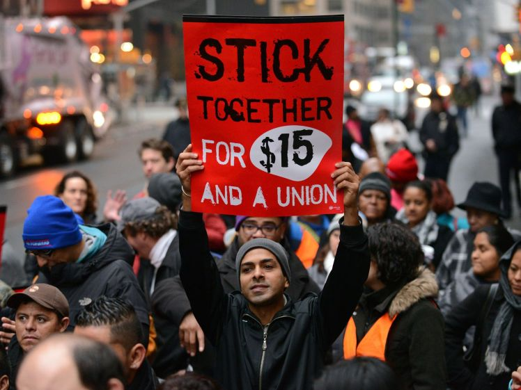 A protester in New York holds up a placard as fast-food workers and union members call for an increase in the minimum hourly wage to $15 and the right of workers to join unions. (Photo: Peter Foley, epa) Source: http://www.usatoday.com/story/money/business/2013/12/05/fast-food-strike-wages/3877023/